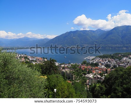 Panoramic view of swiss travel city of LOCARNO in SWITZERLAND and landscape of alpine Lake Maggiore with yacht haven and Alps slopes, cloudy blue sky in 2017 warm sunny summer day, Europe on July.