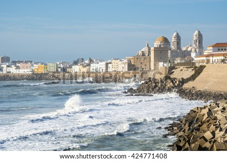 Panoramic view of the ancient city of Cadiz with it's Cathedral. The waves on the winter Atlantic Ocean. Spain - stock photo