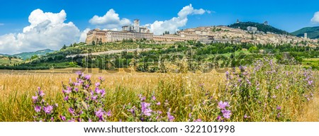 Panoramic view of the ancient town of Assisi with dramatic cloudscape, golden harvest fields and wild flowers, Umbria, Italy - stock photo