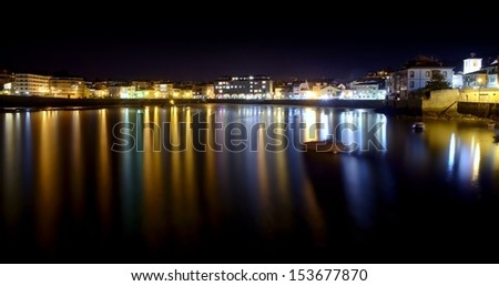 Panoramic view of the beach of Luanco at night, with the reflections of the lights in the sea.