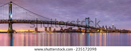 Panoramic view of the Ben Franklin bridge and Philadelphia skyline, under a purple sunset - stock photo
