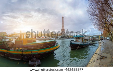 Panoramic view of the Eiffel Tower and Passerelle Debilly bridge from the river Seine embankment, Paris, France. Autumn. Beautiful sitycape in backlit morning sunbeam.