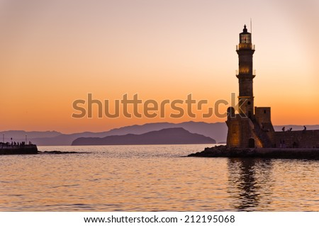 Panoramic view of the entrance to Chania harbor with lighthouse at sunset, Crete, Greece
