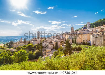 Panoramic view of the historic town of Assisi in beautiful golden morning light at sunrise on a sunny day with blue sky and clouds in summer, Umbria, Italy