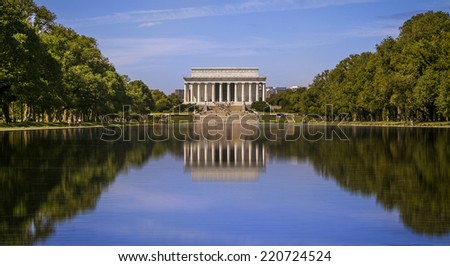 Panoramic view of the Lincoln Memorial in Washington DC in a nice sunny summer day with the water mirror reflecting the architecture of the landmark and its surroundings gardens.