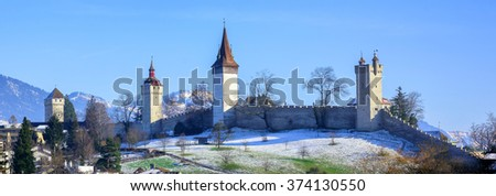 Panoramic view of the medieval city wall and guard towers in Lucerne, Switzerland, on a sunny winter day - stock photo