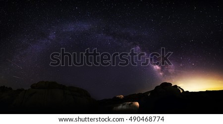 Panoramic view of the Milky Way galaxy on the desert horizon at night. The image depicts a view of the universe and the cosmos with some light pollution on the right side.