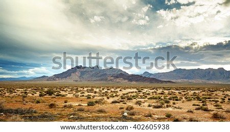 panoramic view of the mojave desert under a cloudy sky - stock photo