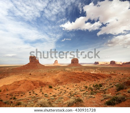 panoramic view of the monument valley under a cloudy sky - stock photo