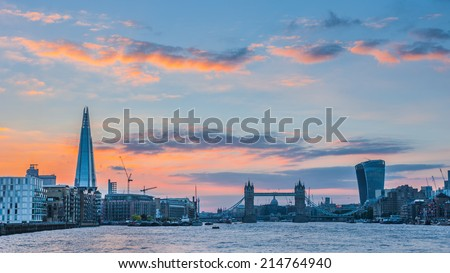 Panoramic view of the new London skyline at sunset with The Shard, Tower Bridge and 20 Fenchurch Street under dramatic sky. - stock photo