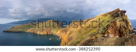 panoramic view of the ocean coast of Madeira island, Portugal, with dramatic sky and dry cliffs - stock photo