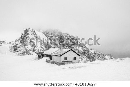 Panoramic view of the Tyrolean wooden house and rocks behind at the end station of the funicular on the peak Hafelekar (Nordkette). The sad winter landscape - snowfall, deep snow, frosty, Austria