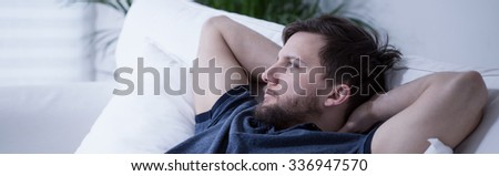 Panoramic view of thoughtful man lying on bed