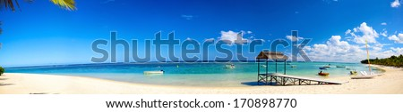 Panoramic view of tropical beach with jetty and boats - stock photo