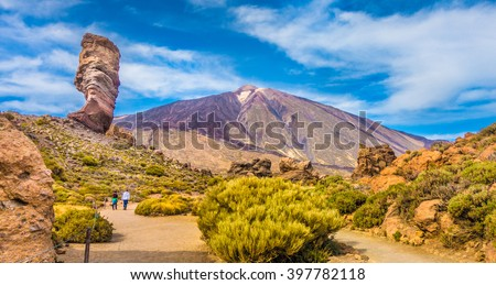Panoramic view of unique Roque Cinchado unique rock formation with famous Pico del Teide mountain volcano summit in the background on a sunny day, Teide National Park, Tenerife, Canary Islands, Spain - stock photo