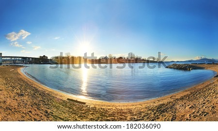 Panoramic view of Vancouver city from the sandy beach side. Sunset above the blue bay - stock photo