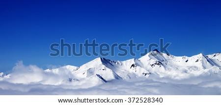 Panoramic view of winter snowy mountains under clouds at nice day. Caucasus Mountains, Georgia, region Gudauri. - stock photo