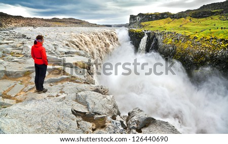 Panoramic view of woman standing near famous Dettifoss waterfall in Vatnajokull National Park, Northeast Iceland