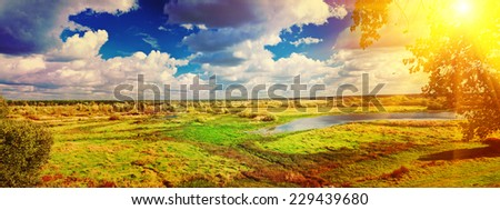 panoramic view on big meadow with small flood sky with sun instagram stile - stock photo
