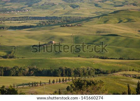 Panoramic view on farmland in Tuscan landscape as the sun sets - stock photo