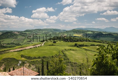 Panoramic view on fields in the Tuscan landscape of the Val d'Orcia overcast by dramatic clouds - stock photo