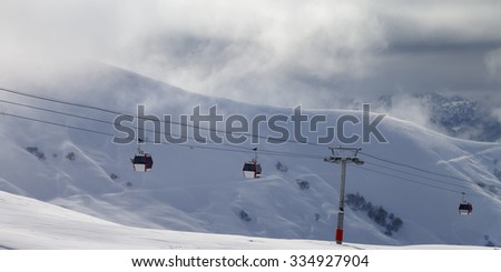 Panoramic view on gondola lifts and off-piste slope in mist. Caucasus Mountains, Georgia. Ski resort Gudauri. - stock photo