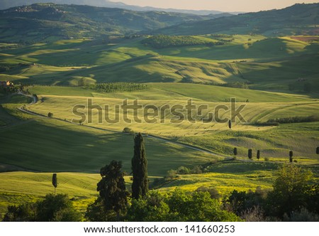 Panoramic view on green fields in Tuscan landscape with shadows falling over the slopes
