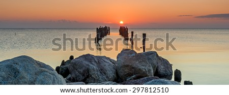 Panoramic view on old broken pier at dawn, Baltic Sea - stock photo
