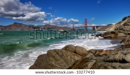 Panoramic view on rocks, Pacific Ocean and Golden Gate Bridge from Baker Beach in San Francisco, USA. - stock photo