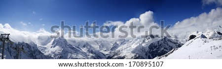 Panoramic view on ski slope in nice sun day. Ski resort Dombay, Caucasus Mountains, Russia.