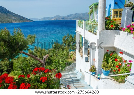 Panoramic view on typical Greek studio with flowers and white teracce having clear view on sea landspace with islands, Greece - stock photo