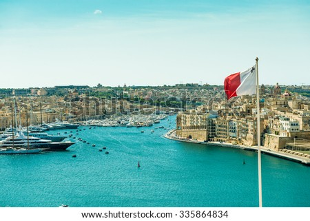 panoramic view on Valletta  with the flag of Malta in the foreground - stock photo