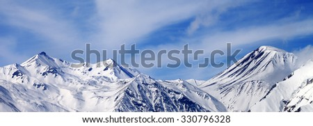 Panoramic view on winter snowy mountains in windy day. Caucasus Mountains, Georgia. Ski resort Gudauri.