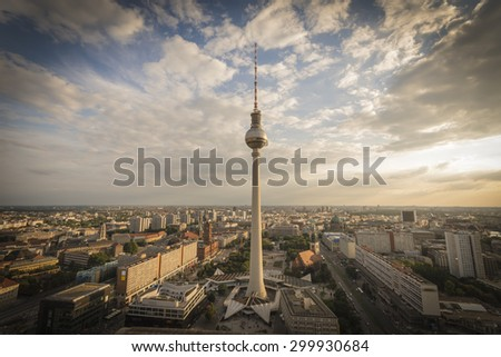 Panoramic view over the Skyline of Berlin with the TV Tower. Photographed at sundown with clouds from the roof of the Park Inn hotel at Alexanderplatz - stock photo
