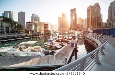 Panoramic view with modern skyscrapers and water pier of Dubai Marina at sunset, United Arab Emirates - stock photo