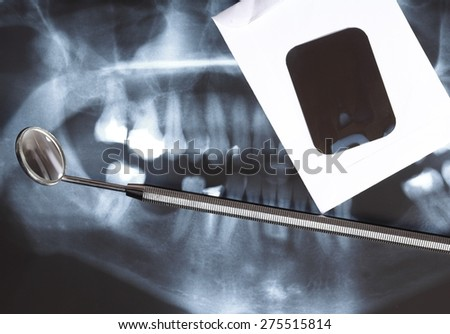 Panoramic x-ray image scan of humans teeth and dental mirror - stock photo