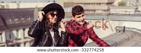 Panorma of young and attractive hipster couple sitting on roof - stock photo