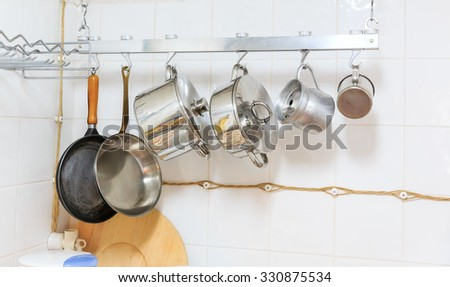 Pans and pots hanging in the kitchen - stock photo