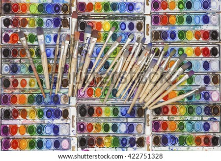 Pans of vividly colored watercolor pans side by side in a grid with an array of well used artist's paintbrushes splayed across the top. - stock photo