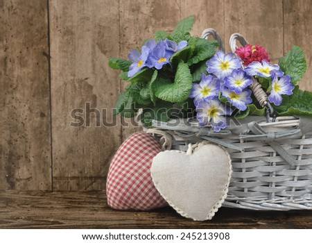 pansies in a basket with a hearts  shaped cushion on a wooden background  - stock photo