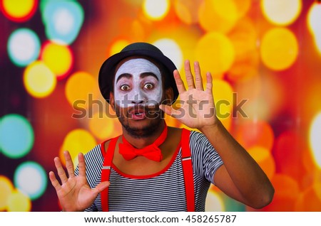 Pantomime man with facial paint posing for camera interacting funny using hands, blurry lights background