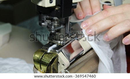 Pantyhose Manufacturing - Woman Sewing. Textile industry. Close up portrait of hands of seamstress sewing using industrial sewing machine. - stock photo