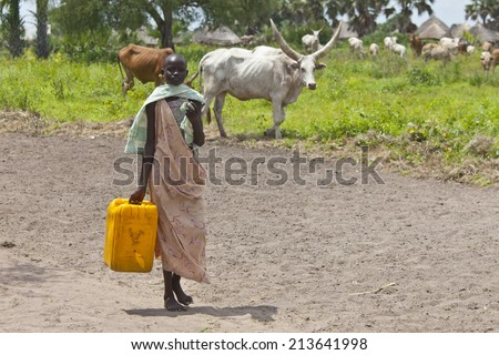 PANWEL, SOUTH SUDAN-JUNE 23 2012: Unidentified woman carries a large water jug to get water from the Nile in South Sudan - stock photo