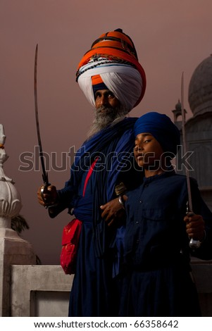 Paonta Sahib, India - May 22, 2009: The gurudwara leader with large colorful turban and a young student holding swords at the Paonta Sahib Gurudwara, famous for its past warriors