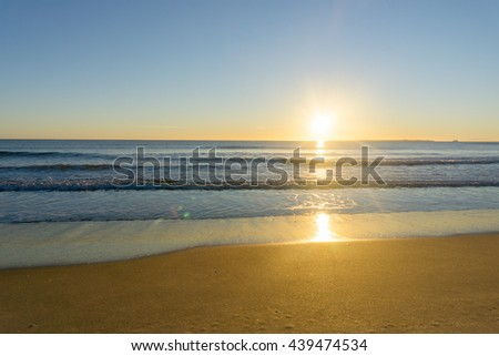 Papamoa Beach, outlook across beach to horizon beautiful golden glow into sunrise