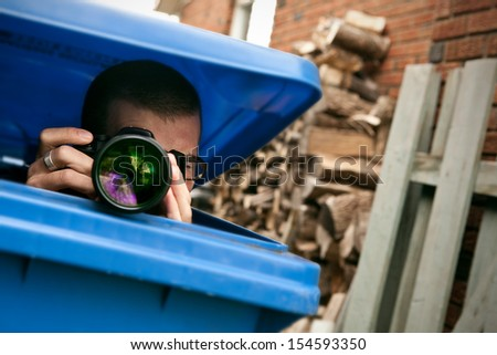 Paparazzi hiding in a blue garbage bin to take pictures - stock photo