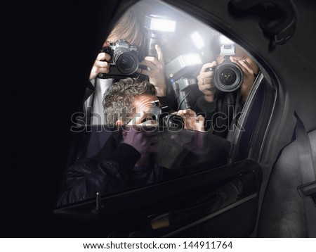 Paparazzi taking pictures through car window - stock photo