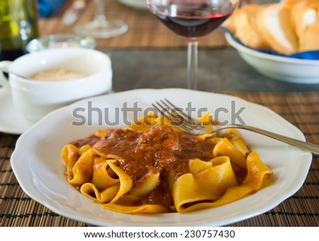 Papardela with meat sauce, parmezan, glass of red wine and bread at Pienza restaurant.  - stock photo