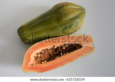 Papaya cut in half with another papaya next to it
