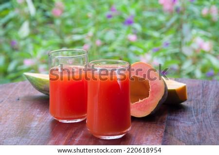 Papaya juice in glass on wood table - stock photo